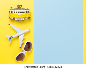 Travel concept backdrop with airplane, sunglasses and tram toy. Top view flat lay with copy space