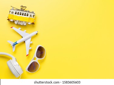 Travel concept backdrop with airplane toy, tram, sunglasses and headphones. Top view flat lay with copy space