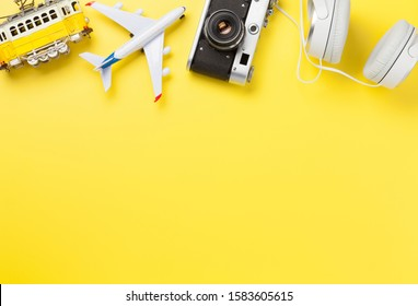 Travel concept backdrop with airplane toy, tram, camera and headphones. Top view flat lay with copy space