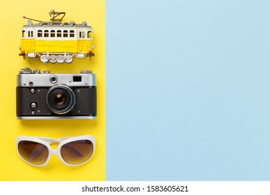 Travel concept backdrop with airplane toy, sunglasses and tram. Top view flat lay with copy space