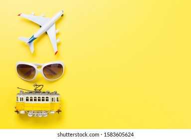 Travel concept backdrop with airplane toy, tram and sunglasses. Top view flat lay with copy space