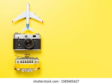 Travel concept backdrop with airplane toy, tram and camera. Top view flat lay with copy space