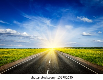 Travel concept background - road in blooming spring meadow on sunset