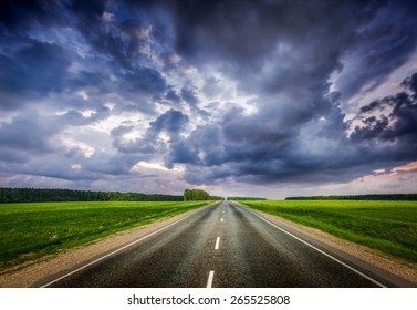 Travel concept background - road and stormy dramatic sky