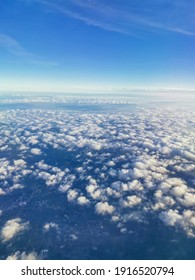 Travel concept. A beautiful view from an airplane on white voluminous fluffy clouds against the background of a bright blue sky, city skyscrapers below, top view, vertical frame