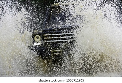 Travel concept with big 4x4 car. Mud and water splash in off-road racing. Drag racing car burns rubber. Extreme. Off-road car. Jeep crashed into a puddle and picked up a spray of dirt
