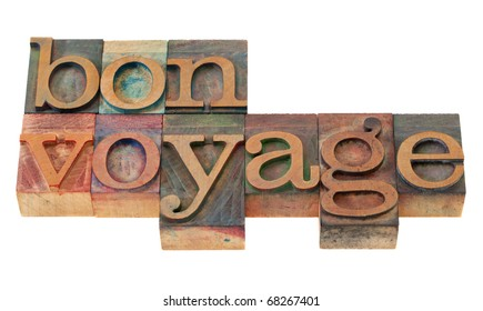 travel concept - bon voyage phrase in vintage wooden letterpress printing blocks, stained by color inks, isolated on white