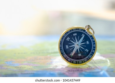 Travel Concept. Close up of compass on world map.