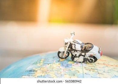 Travel Concept. Close up of motorcycle toy on world map balloon