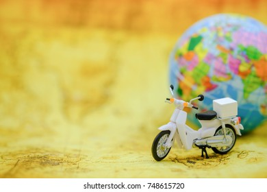 Travel Concept. Close up of vintage motorcycle toy on map with mini world ball.