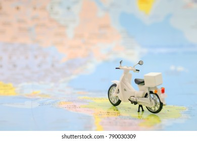 Travel Concept. Close up of vintage motorcycle toy on world map.