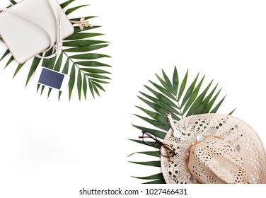 Travel concept, creative arrangement on white background. Palm leaves, handbag, straw hat, mobile phone isolated. Flat lay, top view.