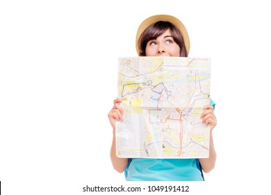 Travel concept. Dreaming about journey. Studio portrait of pretty young woman holding map. Isolated on white.