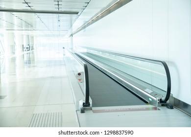 Travel concept. Escalator inside modern international airport terminal.