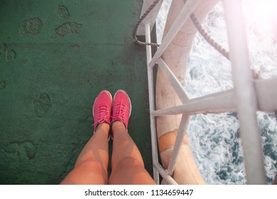 Travel concept. Female feet in sneakers on the background of a sea  landscape sunny summer day.