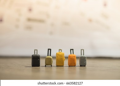 Travel Concept. Five baggage with many style stand on wooden ground with map as background.