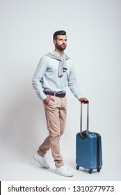 Travel concept. Full length of charming bearded man with a luggage while standing on a grey background. Studio shot