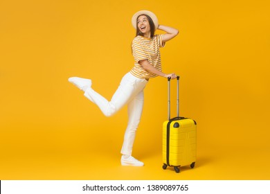 Travel concept. Funny girl jumping, holding suitcase, isolated on yellow background