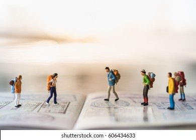Travel Concept. Group of miniature people figures with backpack walking and standing on passport with immigration stamps.
