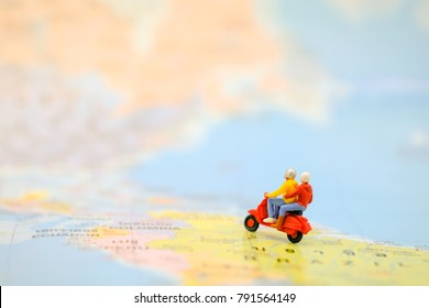 Travel Concept. Group of traveler miniature figures ride motorcycle / scooter on world map.