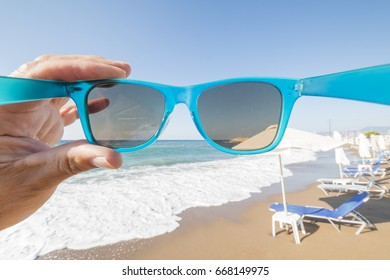 travel concept with a hand holding a  pair of turquoise sunglasses in front of a beautiful beach with sunshades and sunbeds, Latsi beach,  Cyprus island, Greece, Europe