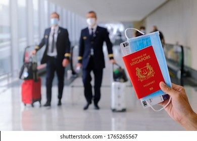 Travel concept. Hand holding Singapore passport, with boarding pass and face mask. Pilots walking in the background with luggage. Reopening; coronavirus covid-19; travel restrictions.
