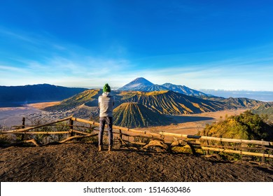 Travel concept of a journey to Bromo mountain in Indonesia - well knowd for landscape beauty and active volcanoes. An Asian male tourist standing relax on the view point
