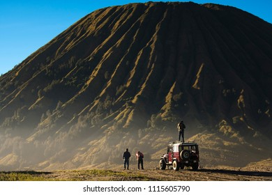 Travel concept of a journey to Mt.Bromo in Indonesia - well knowd for landscape beauty and active volcanoes. An Asian female tourist standing on the car.