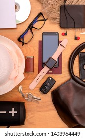 Travel concept. Key, headphones, passport, hat, sunglasses, watch and bag on wooden desk. Background for bloggers. Summer fasion accessories set.