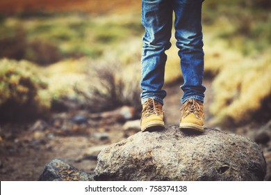 travel concept - little boy hiking boots in mountains
