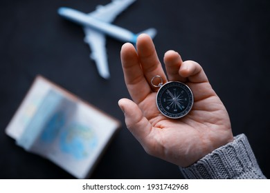 Travel concept. Magnetic compass in the hand. Retro navigator in hand map and airplane background. Adventure Background.