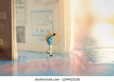 Travel Concept. Male traveler miniature figures with backpack walking on world map with passport with immigration stamps and background.