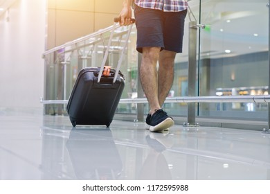 Travel concept, Man in the airports ,young boy or man carries luggage walking at the airport terminal.selective focus,
