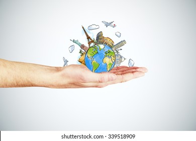 Travel concept with man hand and round earth with landmarks