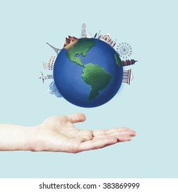 Travel concept with man hand and round earth with landmarks and famous places