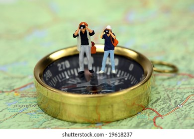 Travel concept. Miniature tourists taking pictures while standing on a compass. There is a map under the compass.