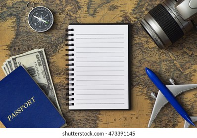 Travel concept with notebook, passport, camera, airplane model, compass and money on world map with copy space.