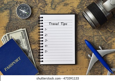 Travel concept with notebook written TRAVEL TIPS with passport, camera, airplane model, compass and money on world map with copy space.