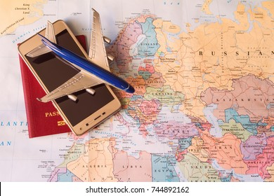 Travel concept on map background. travel plannig. passport, cell phone, toy aircraft on world map. preparation for travel. flight to europe. booking of flight. high season. top view. pasport and plane