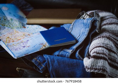 Travel concept. On the suitcase, clothes, passport, map and a camera, book.