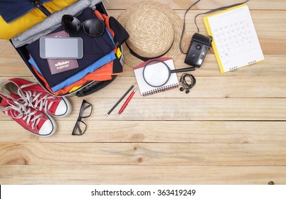 travel concept : Outfit of traveler, student, teenager, young woman or guy. Overhead of essentials for modern young person. Different objects on wooden background.