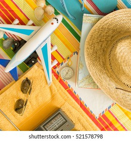 'travel concept - Overhead view of beach vacation tourists kit and related items and airplane - flat lay shot with colorful  background