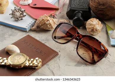 Travel concept passport, map, camera and sunglasses on a light concrete background.