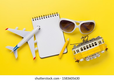 Travel concept with photos, airplane toy, tram and notepad. Top view flat lay with copy space