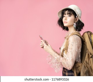 Travel concept portrait of happy woman asian touris on pink background