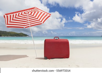 travel concept with a red suitcase  under a red and white striped sunshade at a tropical beach with a turquoise sea, Seychelles, Africa