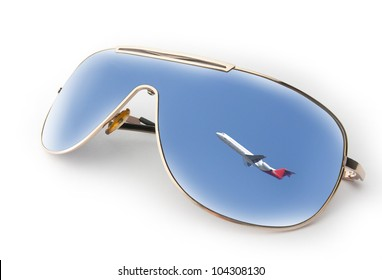Travel concept - reflection of a flying up plane in sky in sunglasses