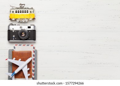 Travel concept with retro camera, airplane, passport and tram toy. Top view flat lay with copy space