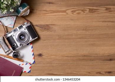 Travel concept with retro camera, film and other on wooden desktop.