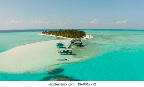 Travel concept: sandy beach on a tropical island by coral reef atoll from above. Onok Island, Balabac, Philippines. Summer and travel vacation concept